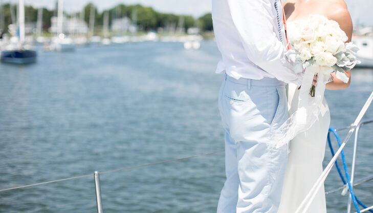 The couple took first-look photos on a sailboat as they cruised through the Milford Yacht Club harbor. The groom wore Bonobos Summer Chinos in light blue, washed navy and white striped suspenders, a peach tie, and a white shirt.