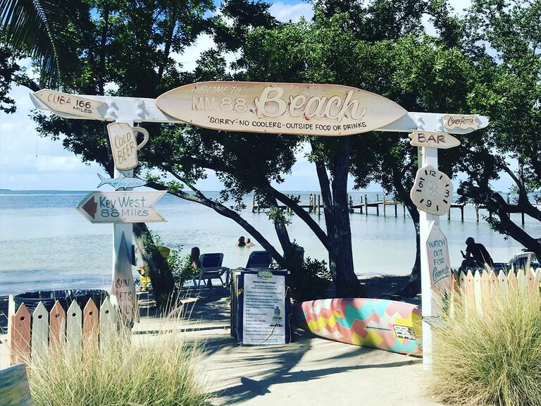 Beach signs and surfboard overlooking the water and trees