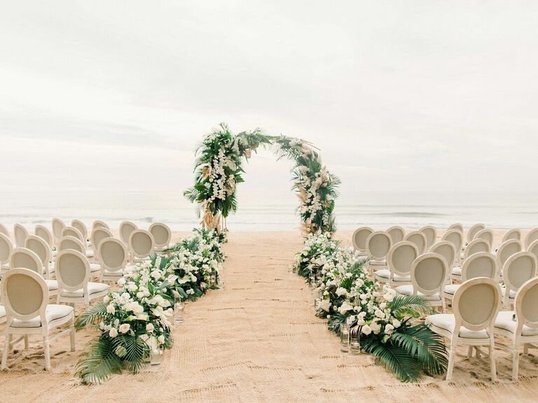 Beach wedding ceremony with upholstered chairs and greenery arch