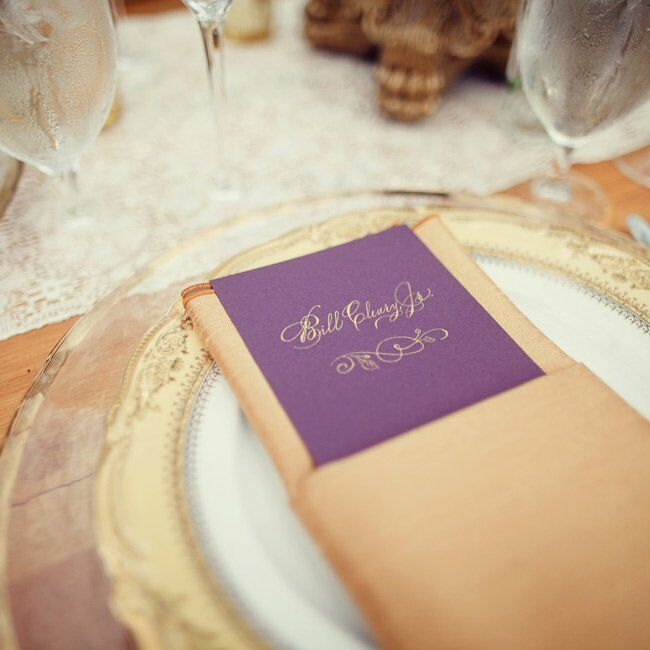 Regal purple-and-gold place settings provided an elegant counterpoint to the rustic elements on the tables.