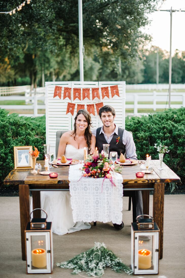 """Shelby and Zack's rustic sweetheart table was made entirely by Shelby and her father. The finished wood table matched their guests' seating with a sweet lace runner, tealight candles and even mini fall-inspired arrangements from 2Birds Events. But there was one distinct difference. """"My abuela [grandmother] had just gone into the hospital the week of my wedding,"""" Shelby says. """"So I had her photo on our table to show her that she made it to my wedding."""" How sweet is that?"""