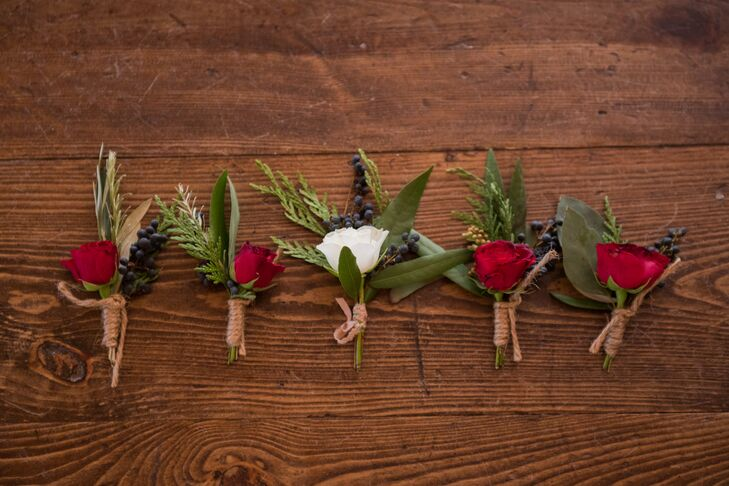 The groomsmen sported burgundy flowers with wintery navy pivot berries, while the groom wore a white rose paired with the same berries. The boutonnieres were all wrapped in natural brown twine.