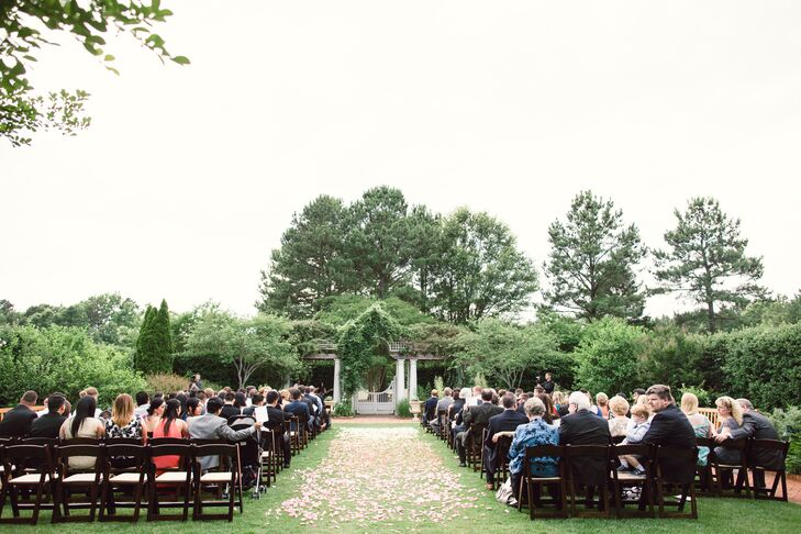 "Christina and Zach exchanged vows in the botanical garden's White Garden, which was surrounded by manicured green hedges. ""We felt like we were in our own secret garden,"" Christina says. ""The space was already naturally beautiful with the white flowers climbing over the trellis."" The couple decorated simply by adding wooden folding chairs and a rose petal aisle."