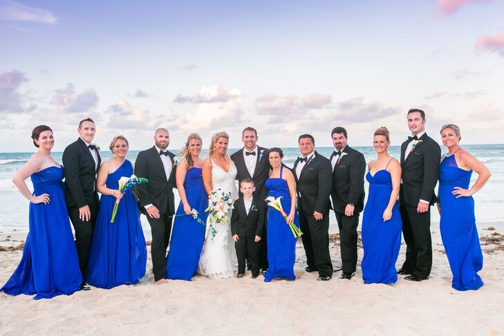 Building on their beach-chic inspiration, Ashley and Phil chose formal looks for their wedding party following a classic black and vibrant blue color scheme. Their bridesmaids rocked the hue with floor-length chiffon dresses and personalized necklines. Each groomsman stood beside them (one barefoot!) in a black-and-white tuxedo. Their boutonnieres showed off a hint of color with blue orchids and white calla lilies in a coral wrap.