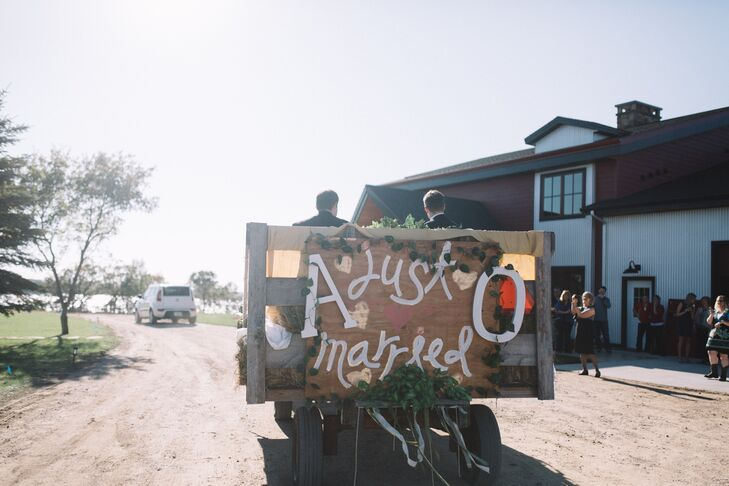 """A barn wedding isn't complete without a """"just married"""" sign on the back of a tractor."""