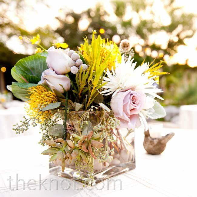 Clear glass vases held an eclectic mix of blooms: roses, pincushion proteas, mums, and succulents.