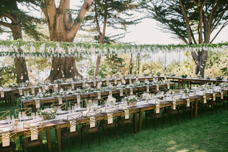 At dinner long, dark brown tables were adorned with a simple cream-colored table runner, gold flatware and chargers, and black and gold chairs. The U-shaped seating arrangement sat under a wooden frame from which a floral garland and Edison lightbulbs hung.