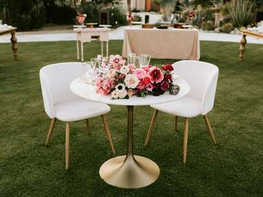 wedding table with two chairs and pink floral centerpiece