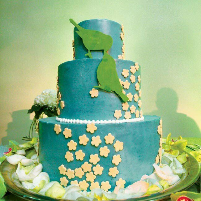 Three circular layers of cake were covered with light blue icing and white trim. Small, cream-colored fondant flowers were randomly displayed on the layers, while two, lime green fondant birds rested on the front of the confection.