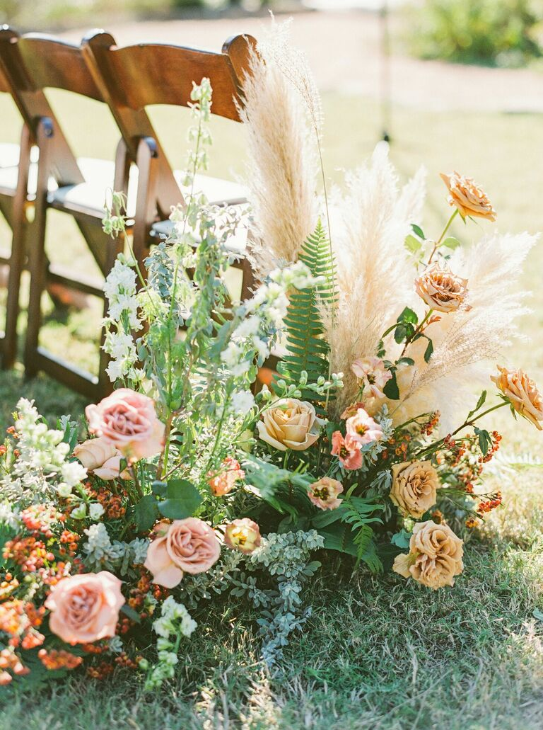 Aisle floral arrangements with roses, ferns and pampas grass