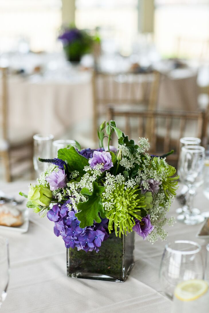 After choosing the flowers for the day, Lauren and Richard chose a navy, purple and green color palette. Their florist, Antheia Floral Design, created the unique centerpieces using purple and green chrysanthemums, hydrangeas, roses and Queen Anne's lace in square glass vases.