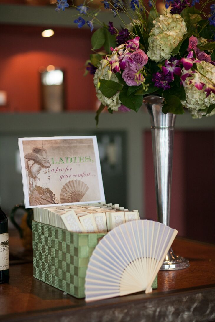 "Keeping with their vintage theme, Lauren and Richard provided guests with handheld fans for the hot July wedding. The small fans were kept in a green box with a sign that read, ""Ladies, a fan for your comfort."""