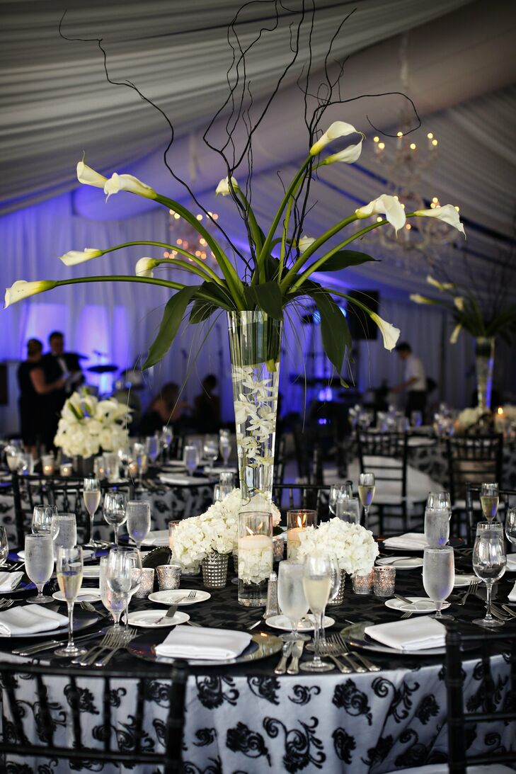 The elegant reception space was draped in gauzy white fabric and decorated with dark tablecloths and tall calla lily centerpieces.