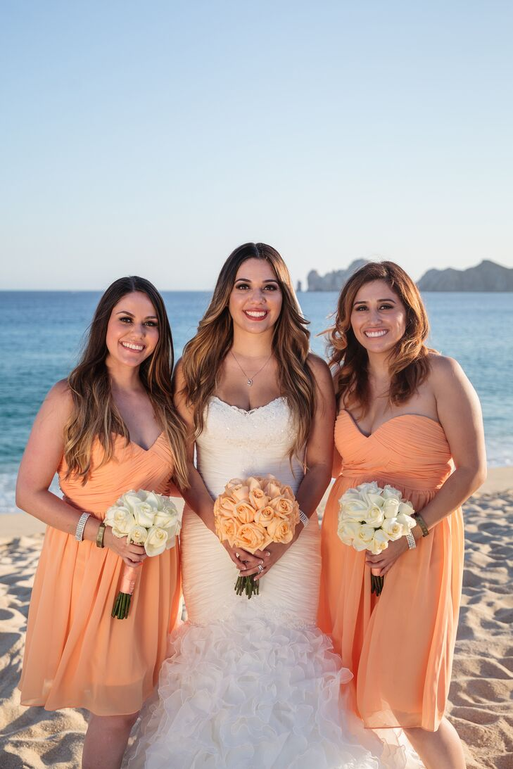Light orange bridesmaids dresses look so pretty on the beach with the blue ocean backdrop. Maria and Maxwell incorporated this color throughout their wedding, even in Maria's light orange rose bouquet.