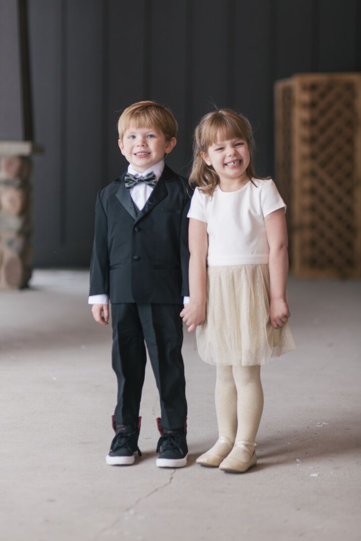 "Three of the ""little party people"" in the wedding wore black tuxedos, black high-tops and dark gray bow ties featuring a truck design; their niece wore an ivory dress with a gold-sparkle skirt and covered up with an ivory faux-fur jacket. She carried a personalized purple bouquet (her favorite color) and changed into sparkly gold light-up high-tops for the reception at Grand View Lodge in Nisswa, Minnesota."