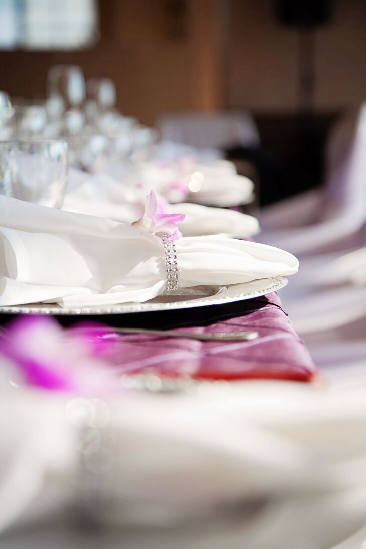 Purple and white orchids were placed at every seat with the crystal-embellished napkin rings.