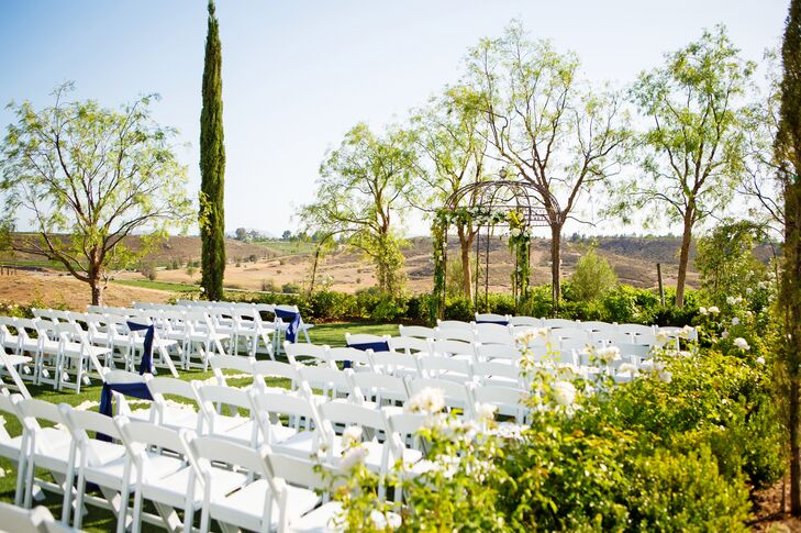 White Folding Chairs Encompassed by Gorgeous Greenery