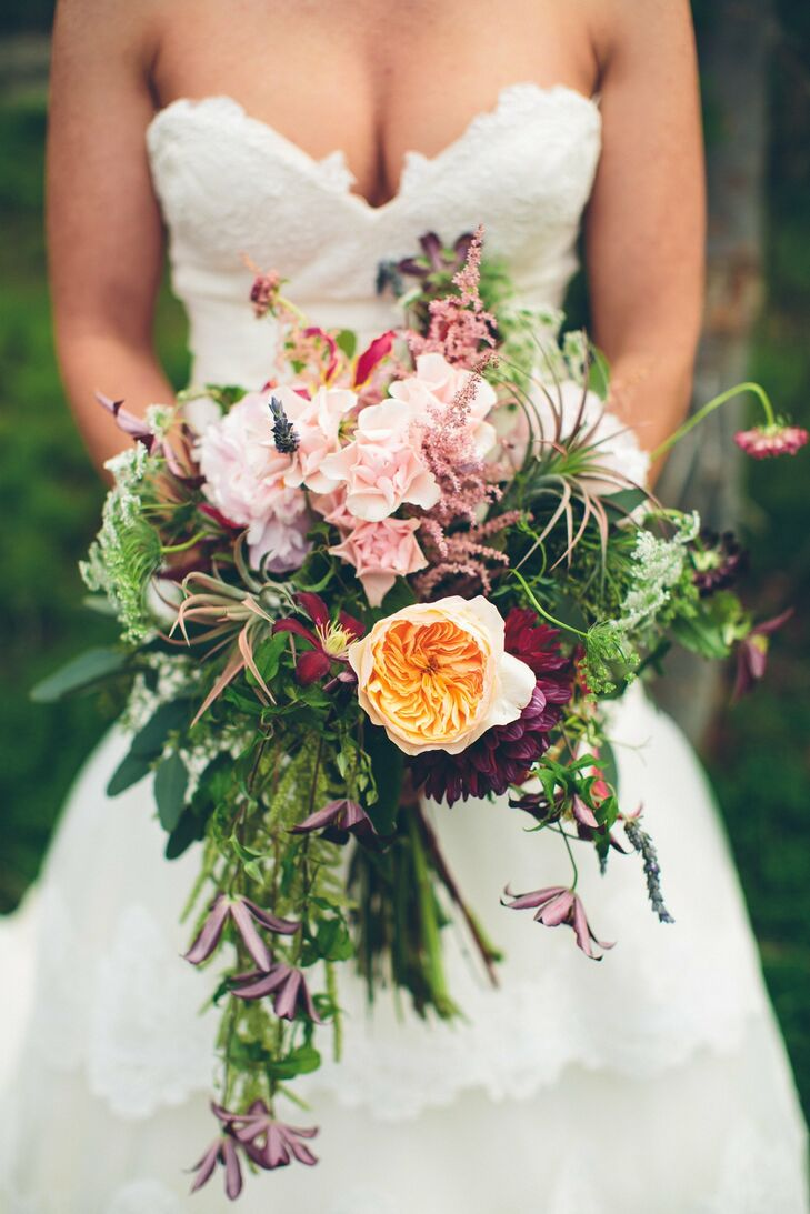 Thistles, peonies, stock flowers and olive branches came together in this uniquely textured bridal bouquet.