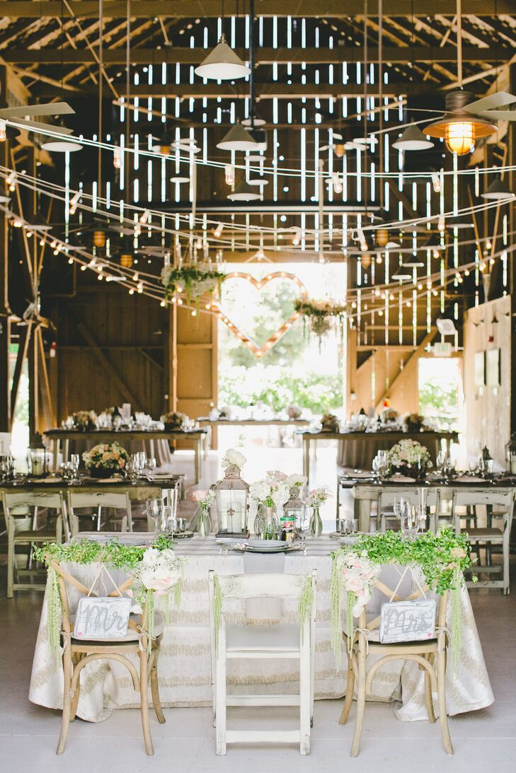 """During the reception, Victoria and Robert took their seats at the sweetheart table. Their antique wooden chairs had """"Mr."""" and """"Mrs."""" white and gray signs that hung from the back, with green garlands draped on top for a rustic, charming vibe."""