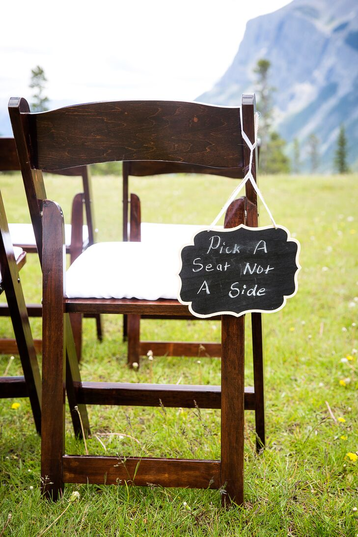A small chalkboard sign letting guests know there was open seating hung off the back of one of the folding ceremony chairs.