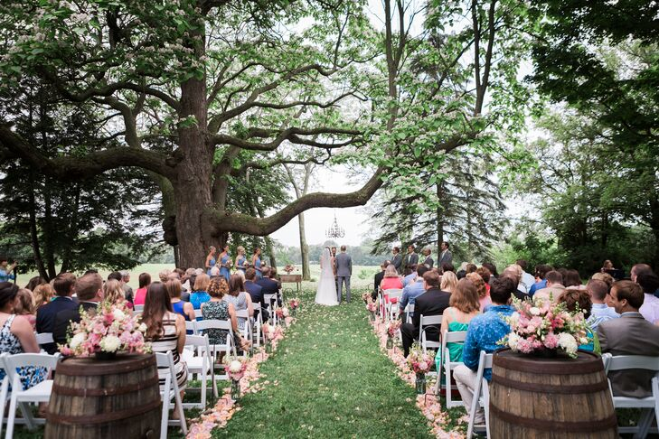 Wooden wine barrels flanked the entrance to the outdoor ceremony, where Megan and Derek exchanged vows under a massive tree strung up with a single ornate chandelier.