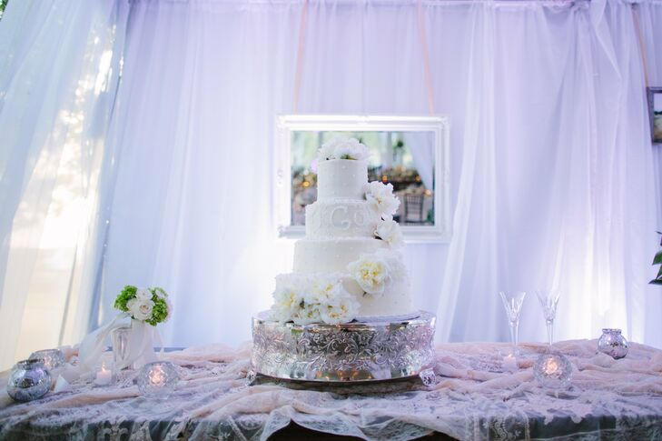 The four-tier wedding cake was decorated with the couple's monogram and topped with fresh flowers.  The entire confection was iced in cream cheese frosting.