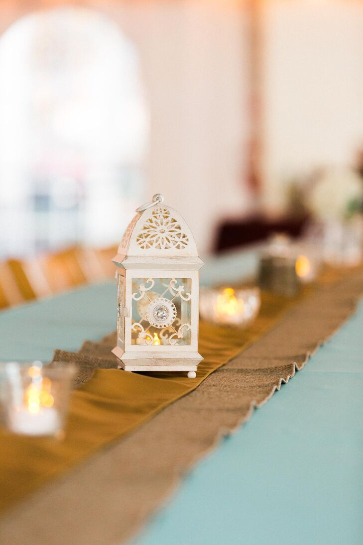 Minimalist centerpieces of small white lanterns and votive candles were arranged on gold satin runners.