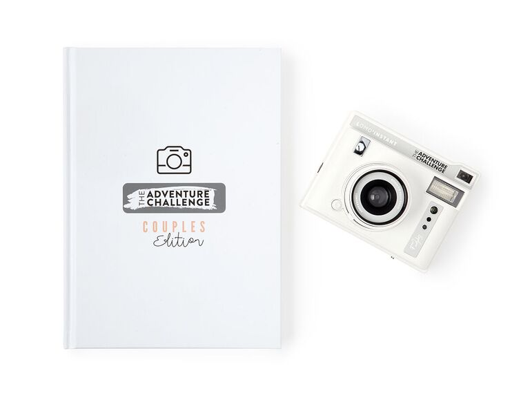 The Adventure Challenge Couples Edition scrapbook next to a camera