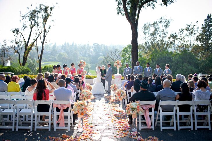 The couple wed overlooking a beautiful golf course - bunches of peach and white flowers lined the aisle.