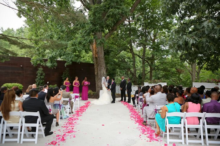 The couple was married in a beautiful outdoor ceremony under the trees. Rose petal accents in shades of lavender and pink were tossed along each side of the aisle.