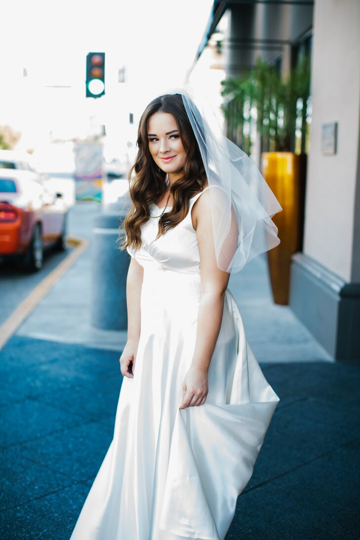 Katie wore her great-aunt's white dress made of a single layer of silk. Her great-aunt got married in the 1960s and borrowed the gown from her own mother, who had worn it in 1943. Although Katie made alterations, she kept the original buttons that trailed down the back.
