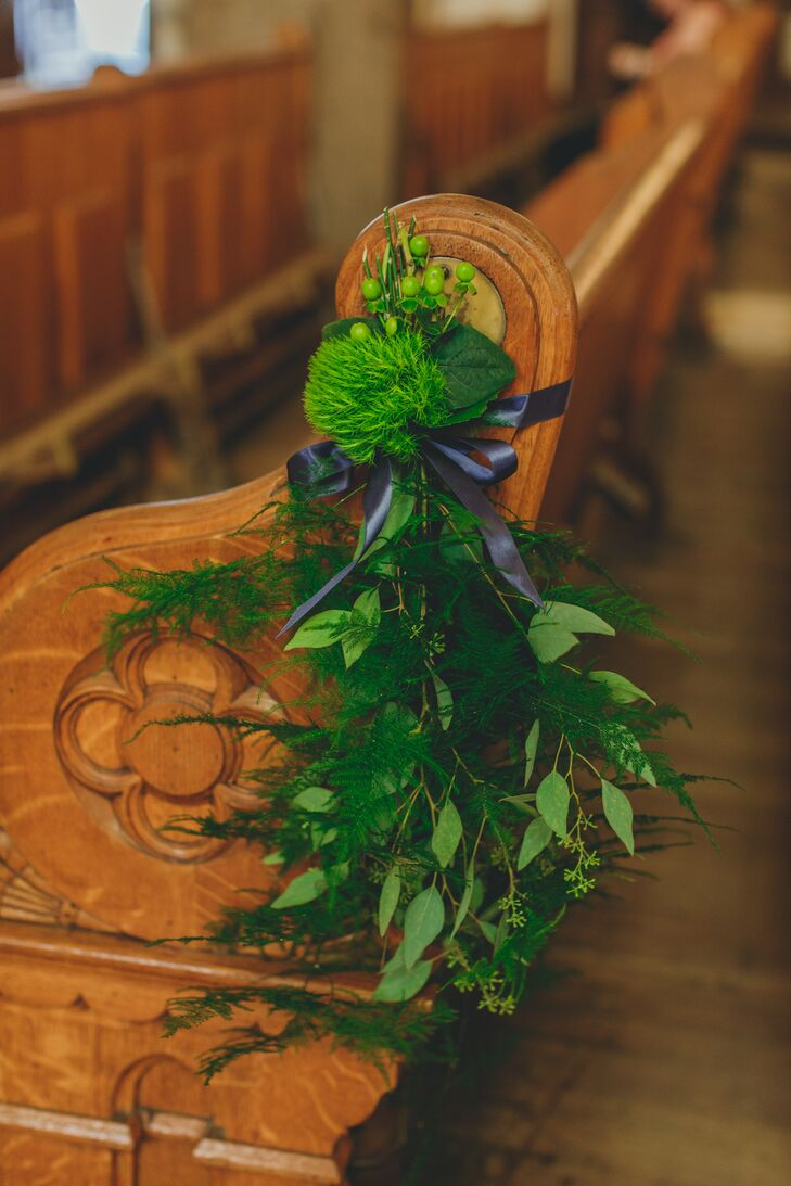 The church aisle was lined with ornate wooden pews, which were subtly decorated with greenery bunches for a natural look.