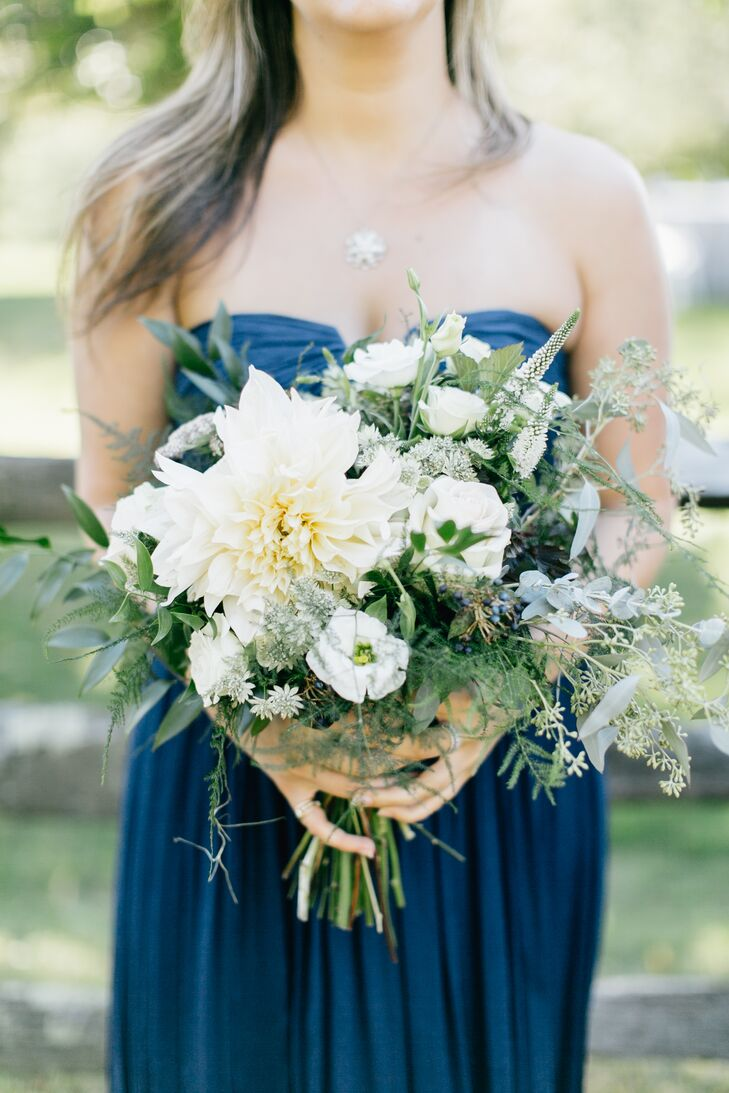 Pops of white blooms, like dahlias, filled the whimsical bridesmaid bouquets that offset the dark navy of their dresses.