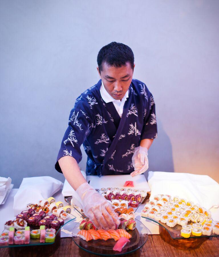 Man making sushi rolls at a wedding