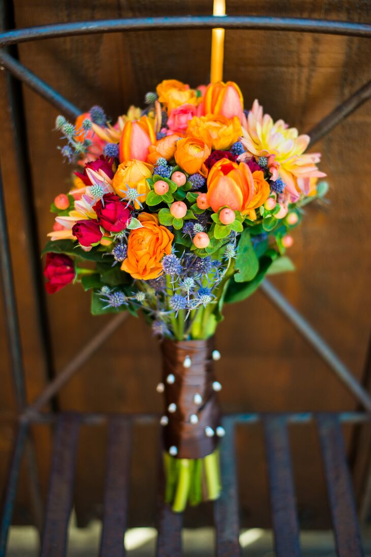 """The bride's bouquet consisted of orange ranunculus, red carnations, peach roses, dahlias, hypericum berries, thistles and greens. """"I wanted the flowers to have a vibrant fall feel and to have an organic look,"""" says Kathleen."""