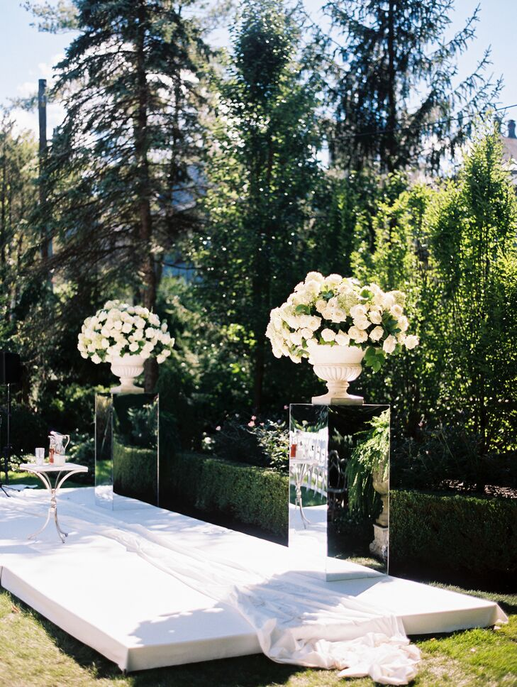 Mirrored Pedestals Holding Urns of Lush, White Blooms