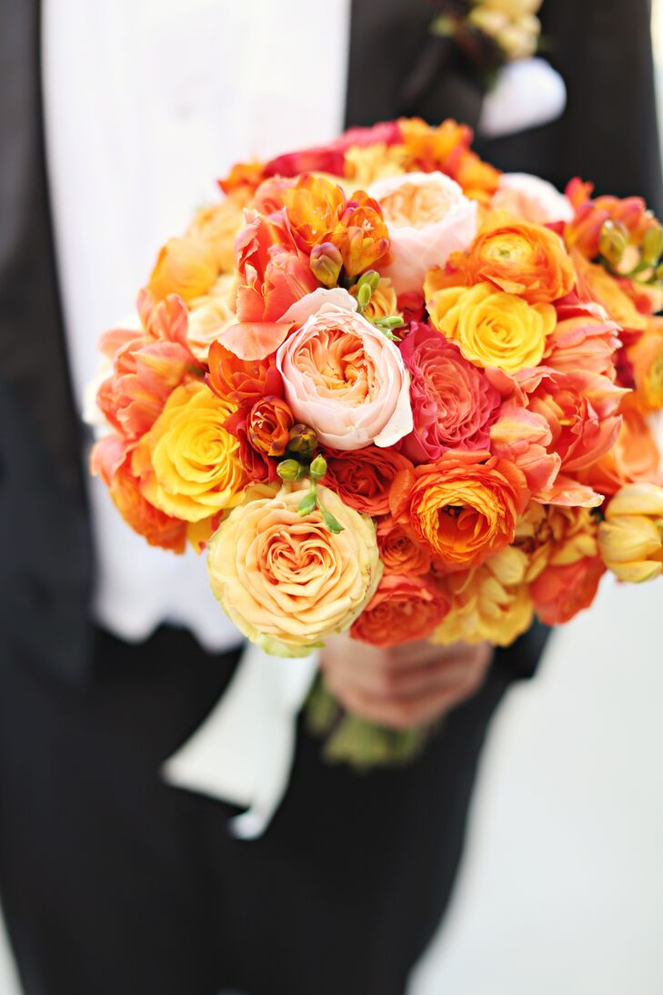 "Kathryn carried a textured orange bouquet of garden roses, dahlias, tulips, spray roses, English roses, freesia and ranunculus. ""With my color palette consisting of all bright, beautiful colors it was important to me that my bouquet look like I was a part of the same story,"" says Kathryn."