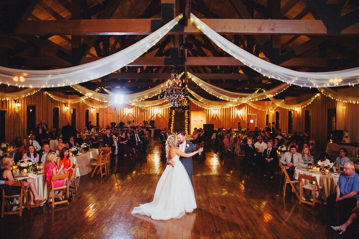 Courtney and Andrew entered the rustic reception hall down a staircase lined with candles, greenery and small bouquets. They shared their first dance on the hardwood dance floor under fabric-draped rafters, surrounded by rectangular and round dining tables.