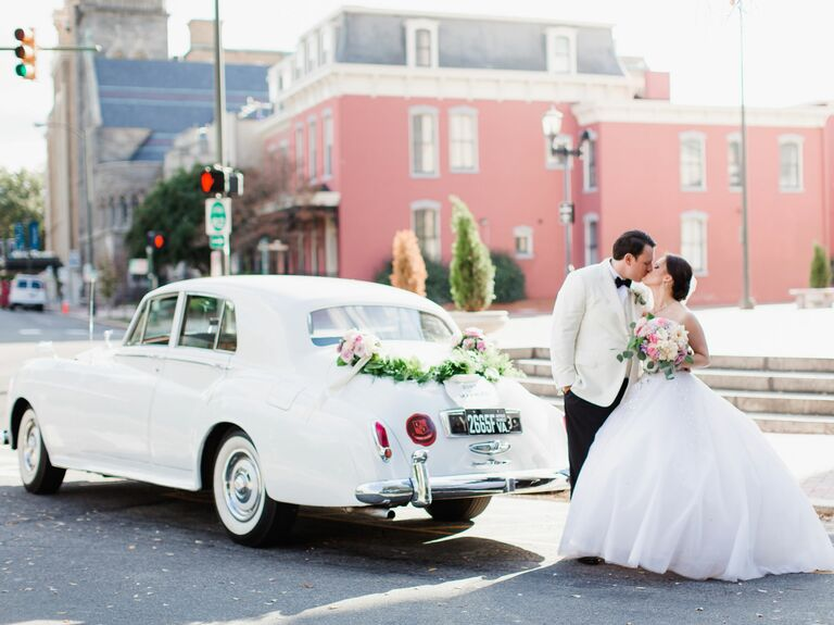 Bride and groom kiss in front of a white retro getaway car