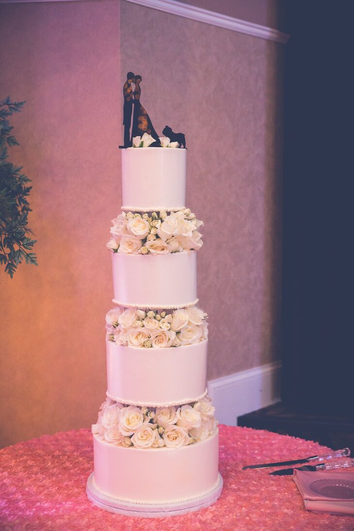 The ivory wedding cake had four identical tiers that were separated by ivory and pink rose arrangements between the layers. On the top of the cake was a black depiction of a bride and a groom with their dog.