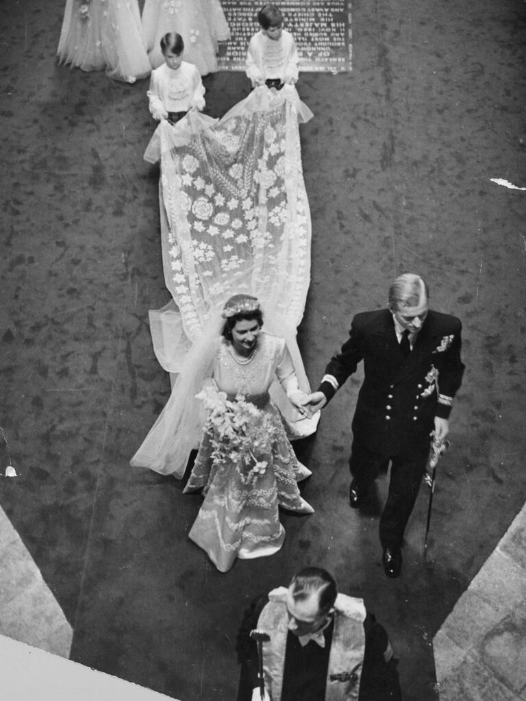 Aerial photo of Queen Elizabeth and Prince Phillip on wedding day walking through Westminster Abbey