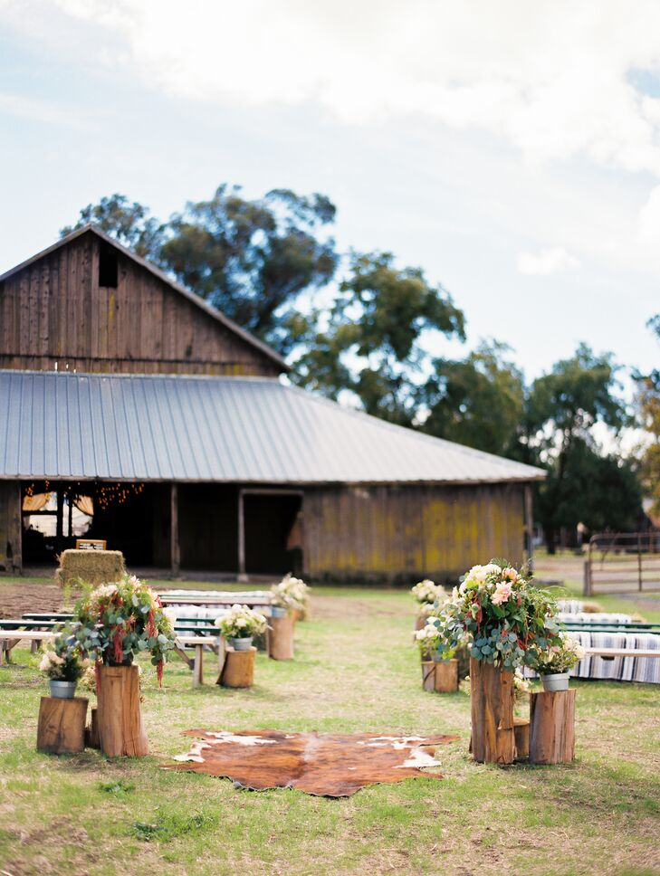"The decor for the outdoor ceremony near the barn was recycled: ""I set aside eucalyptus stumps our venue had piled up from a tree trimming and grouped them together on each side of the altar and on alternating sides of the aisle for the ceremony space,"" Julie says. ""We placed flower arrangements on top to soften them up."""
