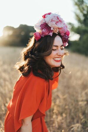 Bride Smiling in a Field While Wearing Pink Flower Crown