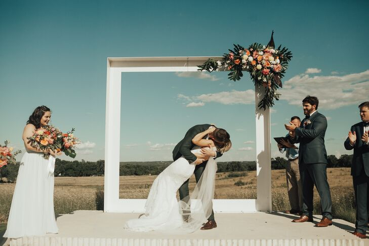 Jordyn and Kyle shared their first kiss under a sleek, contemporary white wedding arch adorned with an orange and pink corner floral arrangement.