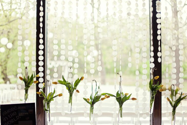 Vases of yellow tulips hung at different lengths from strings of frosted glass circles and decorated floor to ceiling windows.