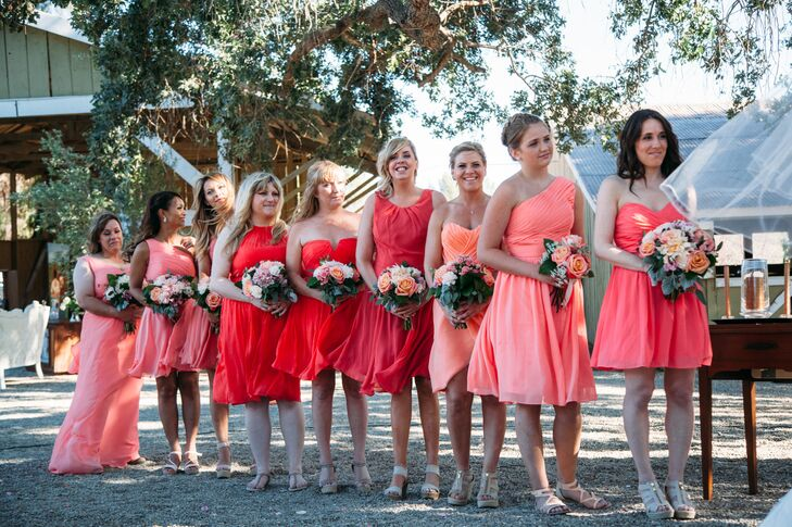 All the bridesmaids wore knee-length dresses in an array of colors—ranging from a light pink to red. They wore the gowns in several different styles, worn with open-toe shoes.