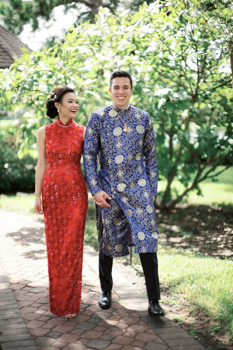 Couple in traditional Chinese wedding attire holding hands and walking