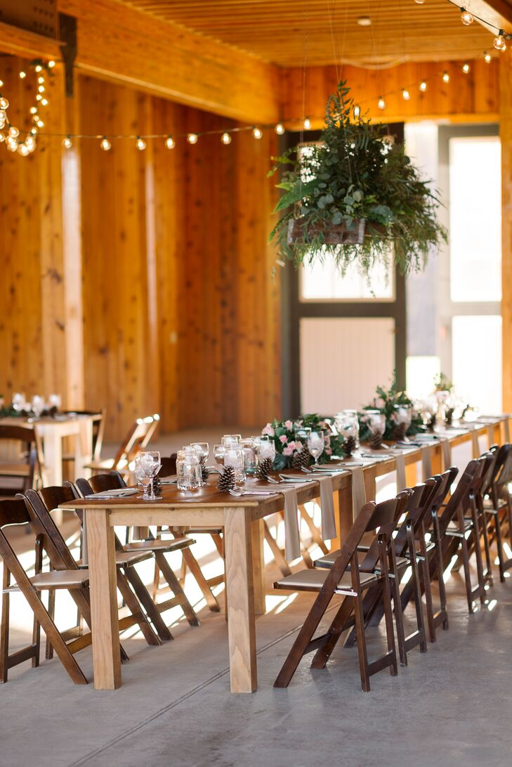 """The brides decked out their rustic barn venue in flowing arrangements of greenery and flowers, along with romantic string lights. """"The overall theme of our wedding was definitely simplicity, and that's what inspired our reception look,"""" Emma says."""