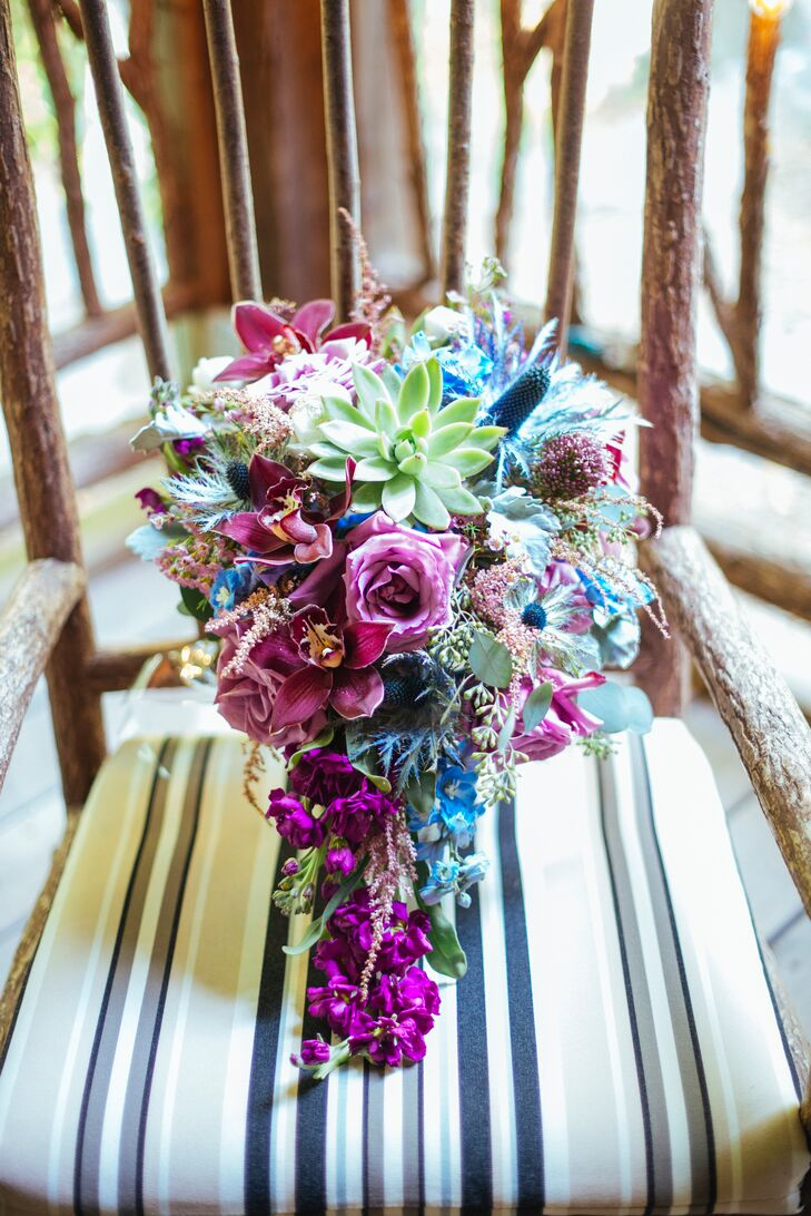 Claudia carried an oversize bouquet filled with blue thistle, succulents, and cascading flowers.