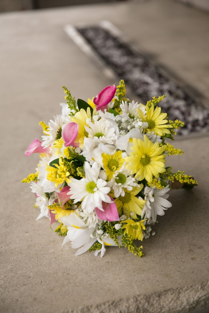 Katie carried a colorful bouquet of bright spring blooms during her April wedding to Travis. The arrangement included an abundant mix of yellow daisies, pink calla lilies,  and various wildflowers.